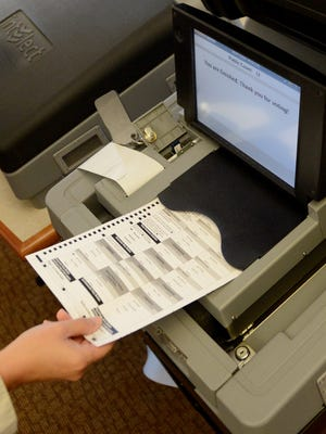 Sample ballots are run through voting machines during testing at the Allouez Village Hall on Thursday.