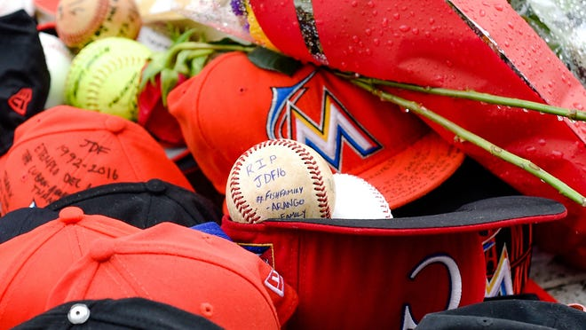 A fan leaves message on a baseball in honor of Miami Marlins starting pitcher Jose Fernandez who was killed in a boating accident over the weekend.