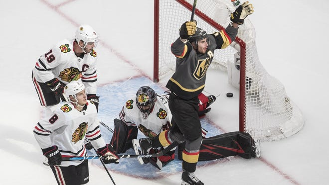 Vegas Golden Knights' Reilly Smith (19) scores on Chicago Blackhawks goalie Corey Crawford (50) as Blackhawks' Jonathan Toews (19) and Dominik Kubalik (8) react during overtime on Thursday.