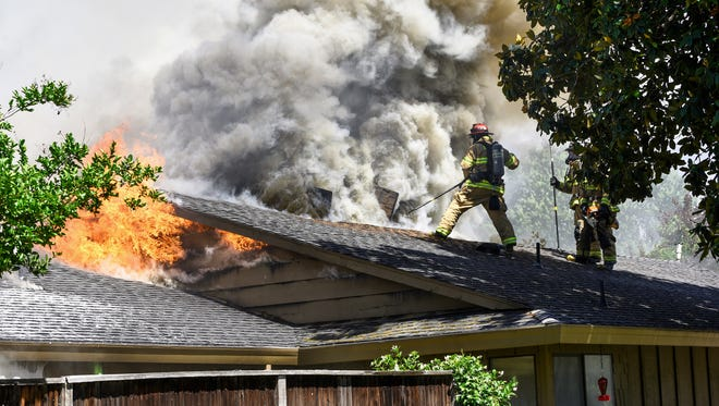 Redding firefighters battle back flames that burned an unoccupied home on Riverside Drive on Saturday afternoon.