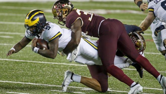 Michigan quarterback Joe Milton (5) leaps forward as Minnesota defensive lineman Boye Mafe (34) tackles him in the second quarter of an NCAA college football game Saturday, Oct. 24, 2020, in Minneapolis.
