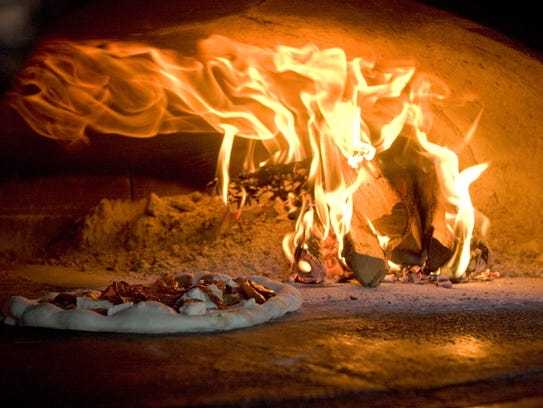 A pizza cooks in the wood burning oven at Pizzeria
