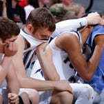 Fulton's Colton Antes, right, consoles Gregg Jones as Zach Walden, left, and Caleb Weldon sit on the bench in dejection during the final moments of their MHSAA Class D semifinal game against Powers North Central Thursday, March 26, 2015, at the Breslin Center in East Lansing, Mich. Fulton fell 71-46.