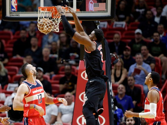 Miami Heat's Hassan Whiteside, center, dunks over Washington Wizards' Marcin Gortat (13) and Otto Porter Jr., right, during the first half of an NBA basketball game, Wednesday, Nov. 15, 2017, in Miami. (AP Photo/Lynne Sladky)