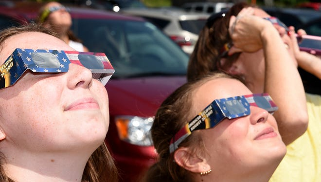 Emily Roelant, left, 15, and her mom Joy, right, check out the start of the eclipse with Kaitlyn Savanyu, 15, at the Lyon Township Library.
