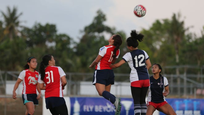 Isla Paint and Roofing Supply Lady Strykers' Alexy Dacanay leaps to clear the ball with a header over Quality Distributors' Tanya Flores during a Round 1 match of the 2016 Bud Light Women's Soccer League Spring season playoffs at the Guam Football Association National Training Center Sunday. The Lady Strykers won 2-0 and will next play No. 1 Personal Finance Center Lady Crushers in the semifinals.