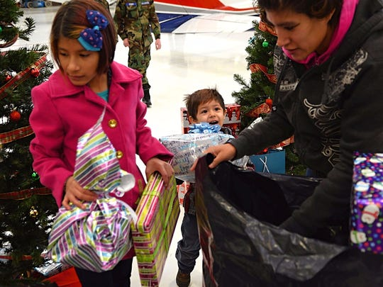 Meream Victoreno, 33, of Reno, (right) and her daughter, Ntatsha Tejeda, 12, and son, Cesar Tejeda, 4, all grab presents and stuff them into a black bag during Operation Santa Claus held on Dec. 9, 2017 at Atlantic Aviation airport.