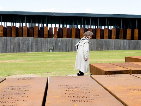 A visitor walks past memorials of lynchings in counties