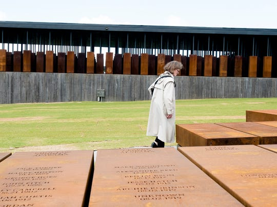 A visitor walks past memorials of lynchings in counties at EJI's National Memorial for Peace and Justice in Montgomery, Ala., on Thursday, April 26, 2018.