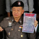 Thai police officer shows a picture of a tattooed human skin which was found in a package of a U.S. tourist, during a press conference at Bangpongpang police station in Bangkok,Thailand. Monday, Nov. 17, 2014. A shipping company in Bangkok put a trio of packages bound for the United States through a routine X-ray and made a startling discovery ó inside were a variety of preserved human parts, including an infant's head, a baby's foot sliced into three sections and a tiny heart.