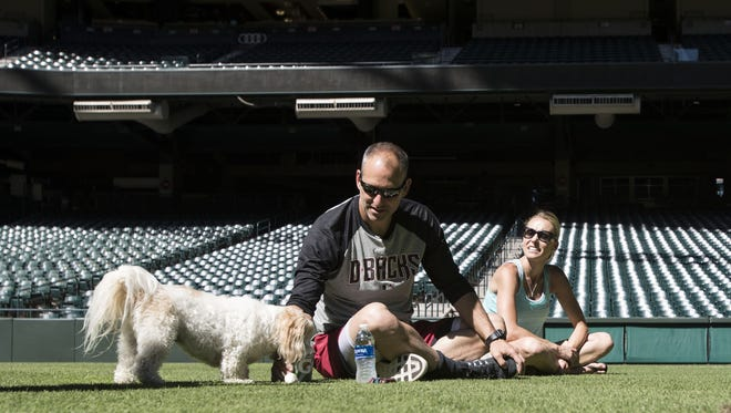 Diamondbacks manager Torey Lovullo and Kristen Lovullo, his wife, play fetch with their dog, B-Lo, inside Chase Field in June 2017.