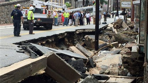 Workers gather Sunday by street damage after flooding in Ellicott City, Md. Historic, low-lying Ellicott City, was ravaged by floodwaters Saturday night, killing a few people, including a Lebanon woman, and causing devastating damage to homes and businesses, officials said.