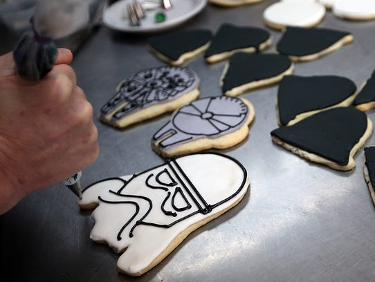 Daleen Grimes decorates a Storm Trooper cookie at her
