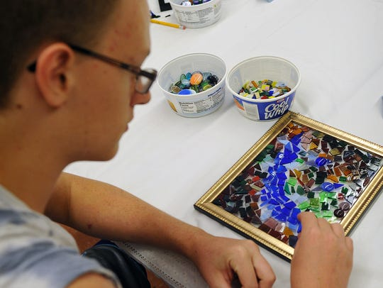 Isaiah Smith designs his stained glass art piece during