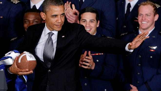 In a 2012 photo, President Obama strikes the Heisman pose after he awarded the Commander-in-Chief Trophy to the Air Force Academy football team.