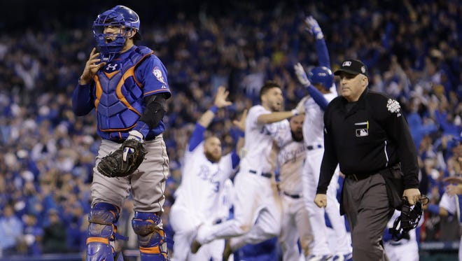 New York Mets catcher Travis d'Arnaud walks off as Kansas City Royals players celebrate Eric Hosmer's game wining sacrifice fly ball during the 14th inning of Game 1 of the Major League Baseball World Series Wednesday, Oct. 28, 2015, in Kansas City, Mo. (AP Photo/Matt Slocum)