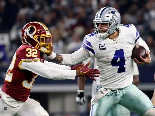 Dec 29, 2019; Arlington, Texas, USA;  Dallas Cowboys quarterback Dak Prescott (4) stiff arms Washington Redskins cornerback Jimmy Moreland (32) during the second half at AT&T Stadium. Mandatory Credit: Kevin Jairaj-USA TODAY Sports