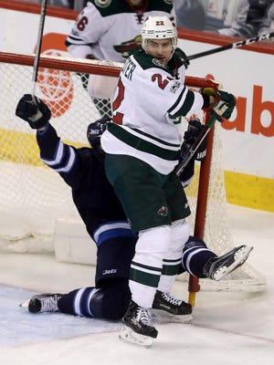 Minnesota Wild right wing Nino Niederreiter (22) knocks Winnipeg Jets defenseman Josh Morrissey (44) into the Jets goal during the first period of an NHL hockey game Tuesday, Feb. 7, 2017, in Winnipeg, Manitoba.