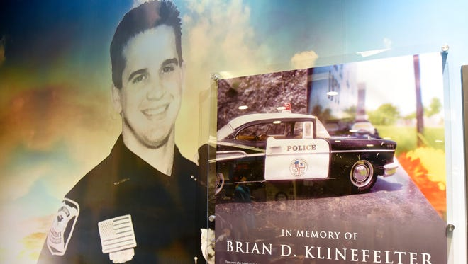 A memorial to Brian Klinefelter fills a wall near the entrance to the St. Cloud store KEEPRS, Several of his family members started the business.