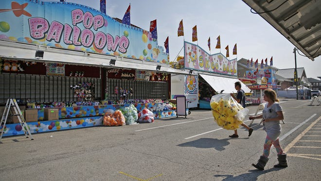 Workers set up on the Indiana State Fair Midway, Thursday, August 3, 2017.