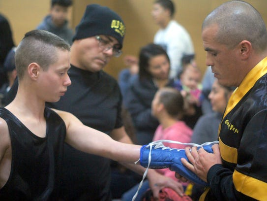Ezekiel Sandoval, 11, gets his hands wrapped by his