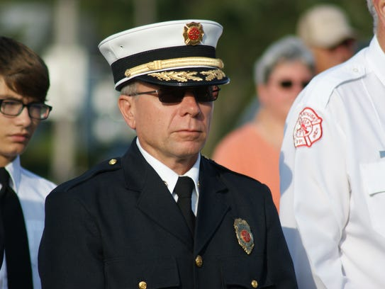 Fremont Fire Chief Dave Foos stands to pay respects