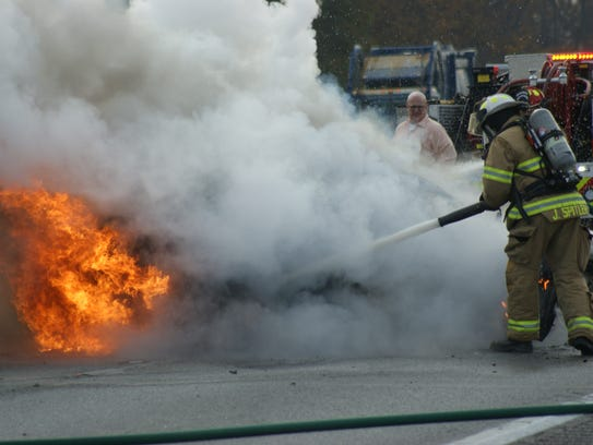 Clyde firefighters extinguish the flames after a Mustang caught fire on U.S. 20 on Nov. 9.