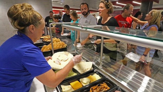 Cafeteria lines like this are unlikely this fall as area schools deal with COVID-19. Shown are Kris Wersel assembling an entree at Waukesha South High School in 2017. The state is recommending individually plated items, if cafeterias open at all.