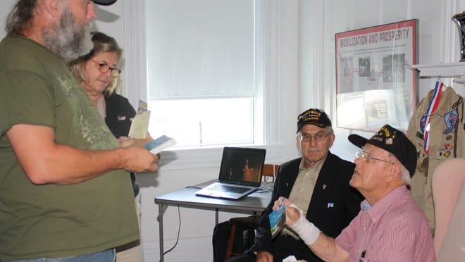 Mark Hahn, of Verona, and Emilie Dressler, of Cincinnati, talk to World War II veterans Donald McMillian and Robert Williams at the Gaines Tavern History Center in Walton Aug. 16.