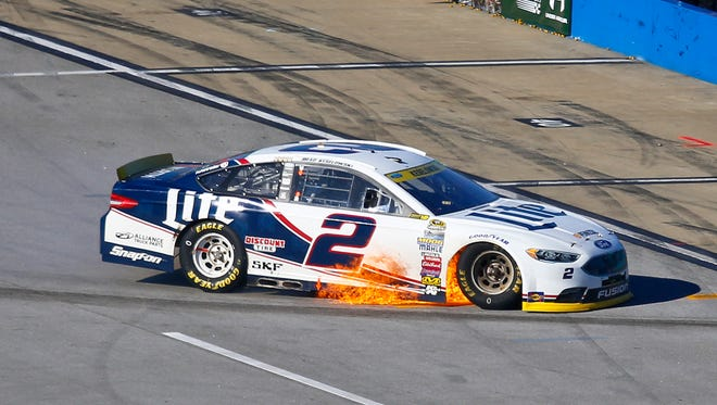 Brad Keselowski (2) drive off the track with flames coming from under his car after his engine blew during the NASCAR Sprint Cup Series auto race auto race at Talladega Superspeedway, Sunday, Oct. 23, 2016, in Talladega, Ala. (AP Photo/Butch Dill)