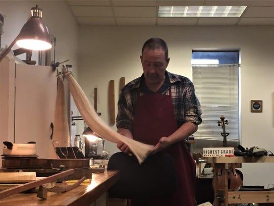 Violin shop owner, John Hawkins, shows the horsehair