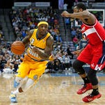 Washington Wizards point guard John Wall (2) guards Denver Nuggets point guard Ty Lawson (3) in the third quarter at the Pepsi Center on Sunday. The Nuggets won 105-102.