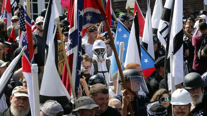 White nationalist demonstrators walk into the entrance of Lee Park surrounded by counter demonstrators in Charlottesville, Va., on Saturday, Aug. 12, 2017.