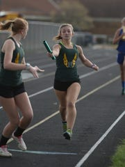 Northeastern's Hailey Coyle, left, takes the baton from Hannah Young in the 4x800m race during the Wayne County Relays track and field meet at Northeastern High School Tuesday, April 29, 2014.