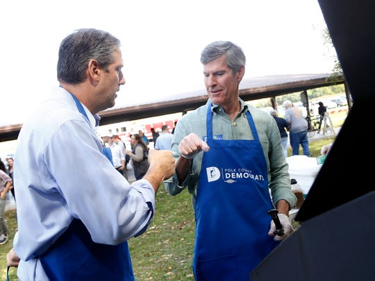 U.S. Rep. Tim Ryan (D-OH) fist bumps Democratic gubernatorial candidate Fred Hubbell as he works the grill Saturday, Sept. 30, 2017, at the Polk County Steak Fry at Water Works Park in Des Moines.