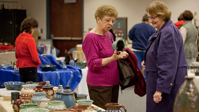 Karen McConnell, of Fort Gratiot, and Karen Galvin, of St. Clair, check out pottery during the Potters Market at St. Clair County Community College in Port Huron.