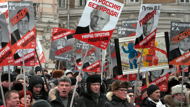"""Demonstrators carry posters of Russian President Vladimir Putin with the words reading """"For Russia without Herod!"""" during a protest rally in Moscow on Jan. 13, 2013. The demonstrators were protesting Russia's new law banning Americans from adopting Russian children."""