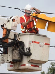 An Oakland County Road Commission worker puts installs
