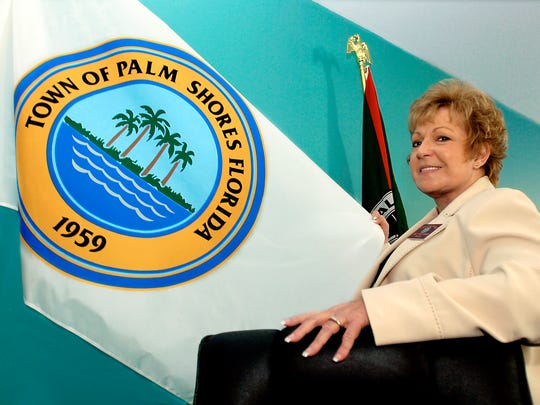 Palm Shores Mayor Carol McCormack holds the town flag in the lobby of Palm Shores Town Hall.