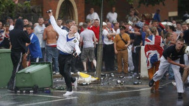 Loyalists attack riot police close to the Ardoyne area of North Belfast, Northern Ireland, Friday, July 12, 2013. Protestant hardliners attacked lines of Belfast riot police as Northern Ireland's annual mass marches by the Orange Order brotherhood reached a furious, chaotic end with running street battles at several urban conflict zones.