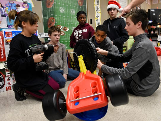 West Valley Middle School students, left to right, Jourdan Rouse, Grant Burgess, McKenna Cook, Kenneth Parker-Smith, Jack Saunders and Jake Greene, construct toys to be donated to the Mission of Hope nonprofit in Amy Crawford's seventh-grade class on Dec. 9, 2014. The students raised funds to purchase the toys for children.