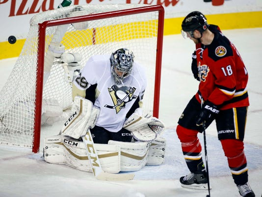 Pittsburgh Penguins' goalie Marc-Andre Fleury, left, looks for the puck as Calgary Flames' Matt Stajan looks on during first period NHL hockey action, in Calgary, on Saturday, Nov. 7, 2015. (Jeff McIntosh/The Canadian Press via AP)