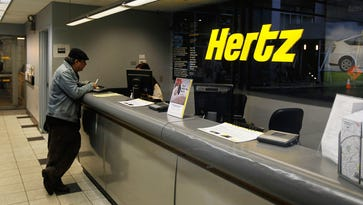 A man stands at the counter of a Hertz car rental location on April 26, 2010, in New York City.