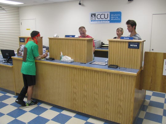 Corning Credit Union tellers Karl Huber, rear left, and Dominic Skakal, under the supervision of Rachael Spencer, prepare to wait on customer Joe Rutan Sept. 29 at the student branch at the GST BOCES Bush Campus in Horseheads.
