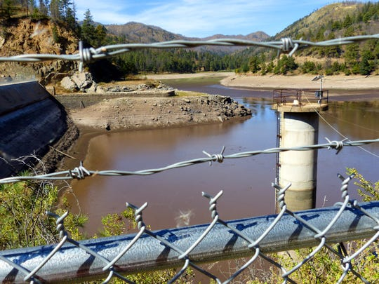 A fence and barbed wire keep the curious away from the dam at Bonito Lake,. With the water nearly drained, only a few ducks paddle on the remaining surface of the lake..