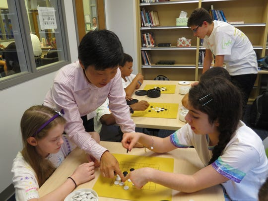 Feng Yun provides some tips on the game of Go to Wardlaw-Hartridge