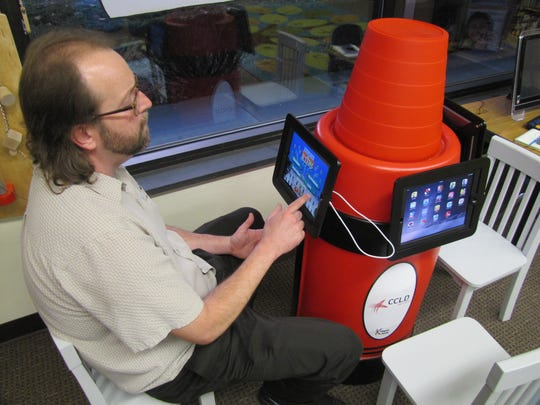 Owen Frank, of the Horseheads Free Library, demonstrates a kiosk with iPads in children's section purchased with an endowment the late Earle R. Catlin managed.