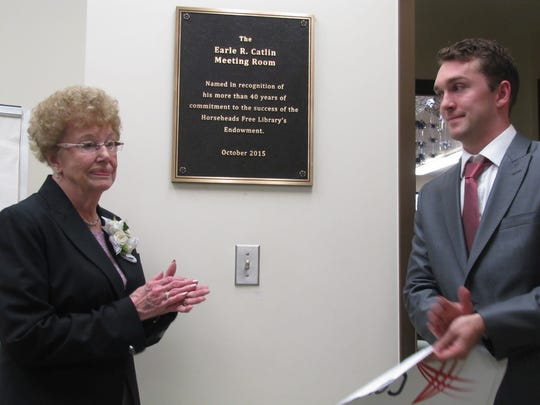 Evelyn Catlin, of Horseheads, and her grandson, Chris Ely of Falls Church, Virginia, stand by the newly unveiled plaque renaming the meeting room at the Horseheads Free Library the Earle R. Catlin Meeting Room.