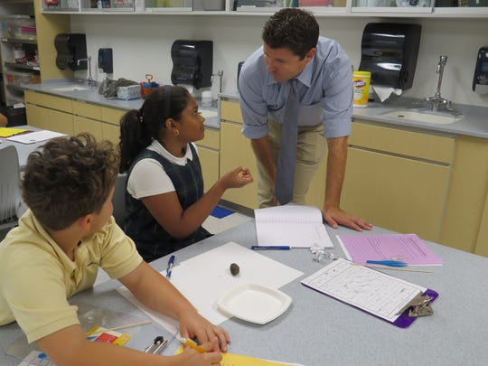 Buzz Gresh of Piscataway and Neha Chandrakanth of Edison, fifth graders at The Wardlaw-Hartridge School in Edison, discuss what they might expect to find when dissecting their owl pellet with teacher Tim Head of Cranford.