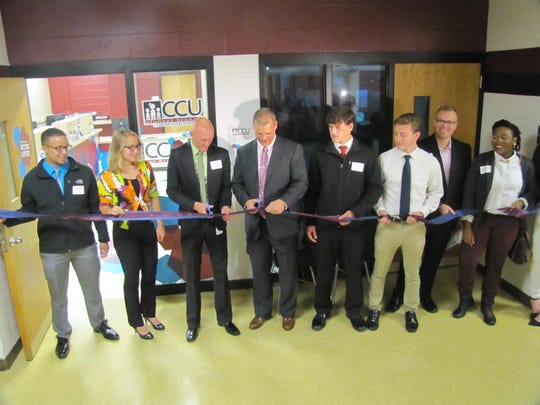Elmira High School Principal Christopher Krantz, fourth from left, cuts the ribbon Thursday for the new student branch of Corning Credit Union. Third from left is Neil Folnsbee, credit union employee who will manage the operation.